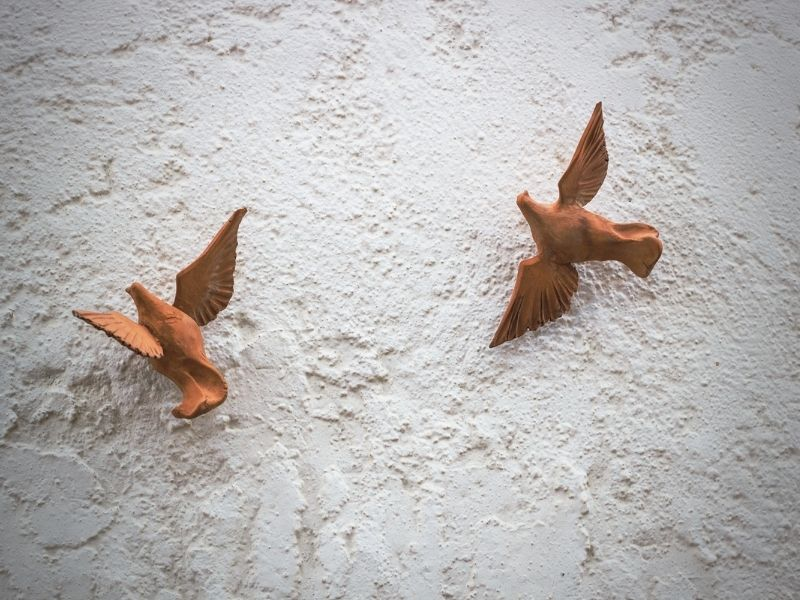 Pair of wooden birds with wings out in flight against a concrete background.