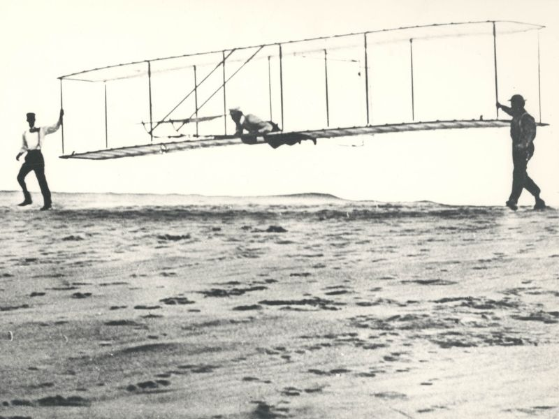 Historic photo of the Wright brothers' third test glider being launched at Kill Devil Hills, North Carolina, on October 10, 1902